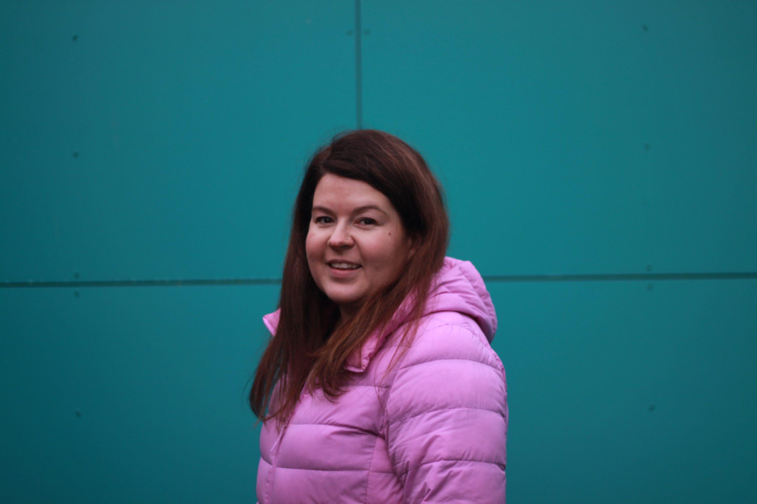 Sonja seisoo vihreää seinää vasten vaalean liila kevyttoppatakki päällään ja hymyilee kameralle